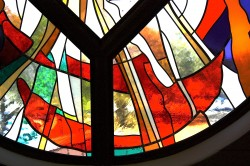 "Detail: west stained glass window, ""Reach Out"". Made from imported mouthblown glass."