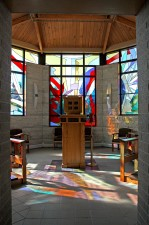 Entrance to octagonal St. Michael Chapel with tabernacle surrounded by stained glass.