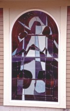 "Daylit exterior view of ""Transfiguration"" showing reflective German opal glass."