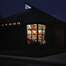 """Creation"": a stained glass window of imported mouthblown German glass at night."