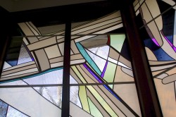 Glass version of straw St. Bridget Cross in Reconciliation Chapel Windows.
